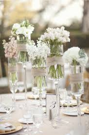 Burlap Wedding Centerpieces by Assorted Wild White Flowers In Tall Stemmed Candle Holders Wrapped
