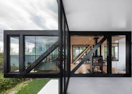 glass box architecture acdf creates quebec home with cantilevered living room