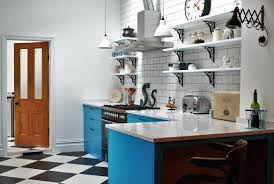a farmhouse sinks brass taps and dark blue shaker cupboards in