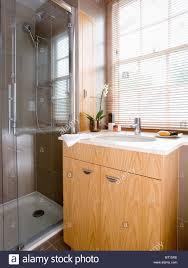 Wood Vanity Units Bathroom by Slatted Blind On Window Above White Basin In Pale Wood Vanity Unit