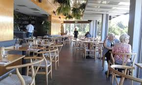 layout of inside of restaurant with bar tables and chairs