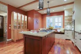 terra cotta colored walls provide contrast painted cabinets