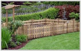 a back garden surrounded by a stone half wall and a trellis style
