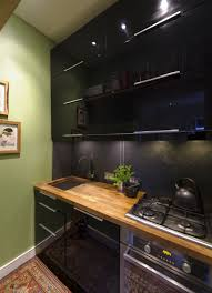 sleek black kitchen cabinets in a small kitchen with butcherblock