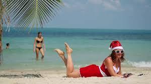 Christmas beach vacation travel woman wearing Santa hat and dress