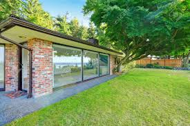 beautiful brick house with glass walls backyard with lawn and