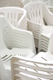 stack of white plastic chairs on the street stock photo picture