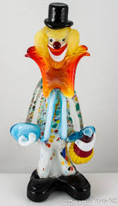 the murano glass clown stands holding a fiasco a traditional
