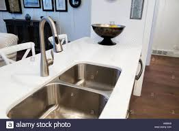a stainless steel sink in a white granite countertop with a bronze