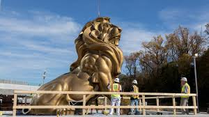 gold lion statues mgm lion statue lowered into place as national harbor resort and