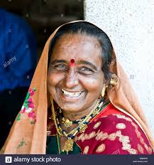 portrait of a senior indian lady seated outside a shop feeling