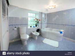 modern tiled bathroom uk with bath bidet and toilet stock photo