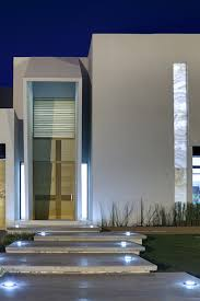 brown cement block home design that has green grass fence in front