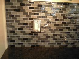this shows a stone tile backsplash with glass inserts on a wet bar