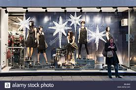 Window Christmas Decorations by Woman Using Mobile Phone Standing In Front Of Shop Window With