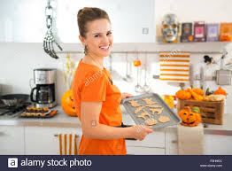 happy young woman holding tray of uncooked halloween biscuits