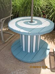 outdoor tables made out of wooden wire spools painted an old wooden spool and with a patio umbrella we found on