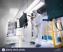 a man in a spray paint booth works on a car repair uk stock photo