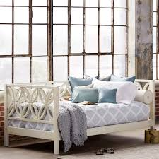white stained wooden daybed with flower pattern accent headboard