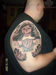 red skull and oakland raiders club tattoo on half sleeve