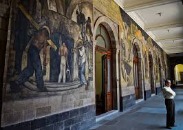 mexico s favorite painters frida kahlo and diego rivera here now a man stands next to murals by mexican artist diego rivera in the education secretariat in
