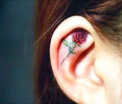 a cute and elegant tattoo of a rose inked inside the ear tattoos