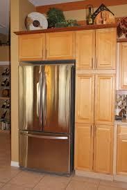 kitchen brown wood pantry white wood tall cabinet black granite