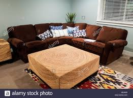 a brown sofa and wicker table in a cozy basement stock photo