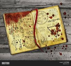 halloween text symbols old alchemy book with bloody hand print and drops lying on wooden