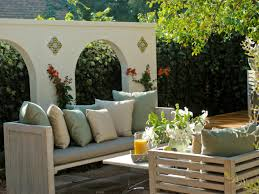 outdoor seat sofa with pillows and table plus a glass vase