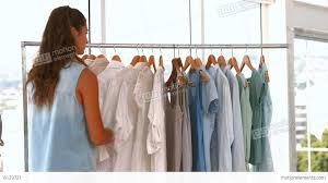 female fashion designer looking at rack of clothes stock video
