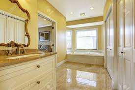 spacious bathroom in tones with windows and shiny tile floor