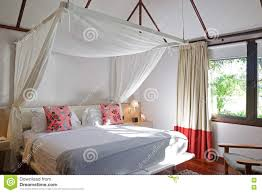 brightly lit bed room of a modern wooden house in tropical country
