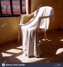 a white towel hanging on a patio chair stock photo royalty free