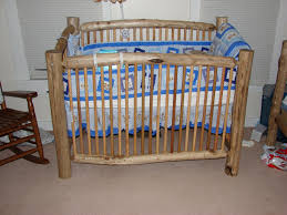 handmade rustic log baby crib with blue and white bedding