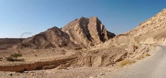 stone desert scenic ridged brown rock at the road in stone desert stock photo