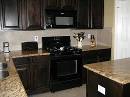 kitchens with black appliances white wall mounted cabinet green