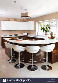 bar stools at breakfast bar in modern kitchen uk home stock photo