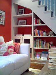 modern under stair storage design with bookshelf and red wall