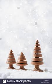 wood turned tree ornaments in snow setting stock photo