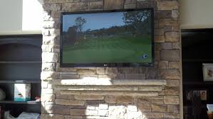 hang a flat screen tv on stone wall over fireplace loversiq