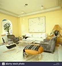Check Armchair Check Rug Over Stool In Pale Yellow Eighties Living Room With Gray