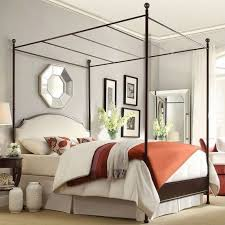 queen size metal canopy bed with white cream linen upholstered