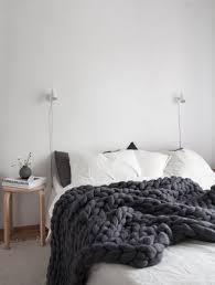 cozy scandinavian style bedroom with super chunky dark grey banket