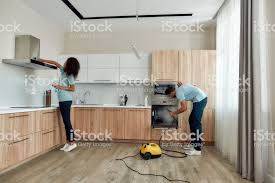 steam cleaning wooden kitchen cabinets your clean home is our business two professional cleaners in working together in the kitchen caucasian using steam cleaner