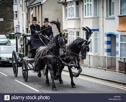 two undertakers riding driving a sombre black victorian era stock