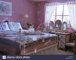 ornate white wrought iron bed with patchwork quilt and cushions in