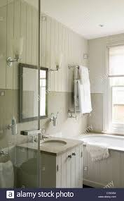 All White Bathroom All White Bathroom With Wooden Panelling And Wall Sconce Lamps