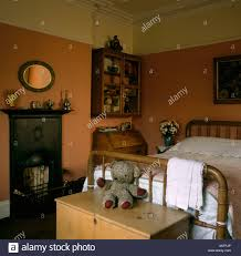 small black fireplace in terracotta bedroom with old teddy bear on