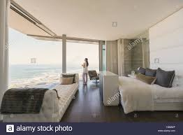 woman looking at ocean view from modern luxury home showcase stock photo woman looking at ocean view from modern luxury home showcase bedroom
